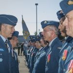 A man wearing a military uniform speaks with other personnel wearing military uniforms who are standing in rows.