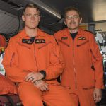 Two men in orange coveralls lean on a bunk in an aircraft.
