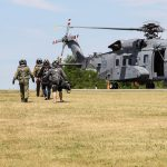 People wearing helmets and carrying items cross a field to the open door of a helicopter.