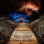 With fireworks in the background, marching bands parade before many spectators seated in bleachers in front of an illuminated stone building.