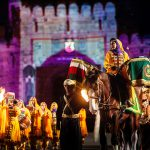 Musicians march and ride horses in front of a large stone building illuminated by coloured lights.