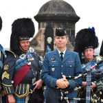 Four men wearing Scottish regalia with medals and badges flank a fifth wearing a blue uniform and holding bagpipes