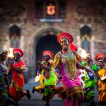 Dancers and drummers dressed in brilliantly coloured costumes perform in front of a stone building.