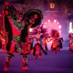 Dancers in brilliantly coloured costumes perform in front of a stone building.