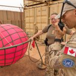 Two Canadian soldiers stand beside a red balloon. One of them is talking into a two-way radio.