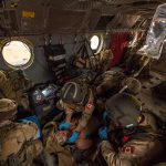 Medical personnel work on a simulated casualty on board a Chinook helicopter while in-flight during training.