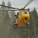 A helicopter hovers in front of trees.