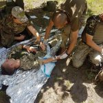 Three Ukrainian soldiers perform a medical procedure as part of an exercise.
