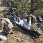 A group of Ukrainian soldiers practice medical procedures in a forest.
