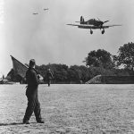 A man holds a flag as a single propeller aircraft approaches to land