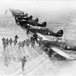 A group of people run towards a line of aircraft.
