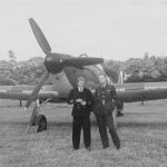 Two men stand in front of a single propeller aircraft.