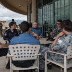 Military members from a variety of countries sit around a table outside