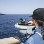 A sailor on board a ship observes the direction in which a nearby ship is sailing.