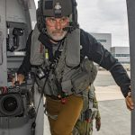 A bearded man carrying a large camera and wearing a helmet steps through a metal doorway.