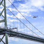 In a blue sky, a helicopter overflies a green suspension bridge.