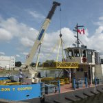 A boat with an onboard crane that is lifting a large metal container.